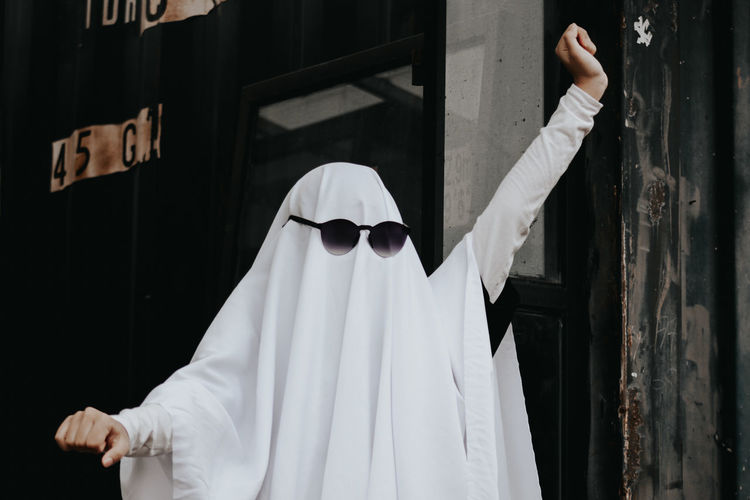 Person wearing white clothing with sunglasses standing outdoors