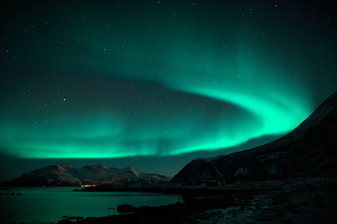 Scenic view of snowcapped mountains and aurora borealis against sky at night