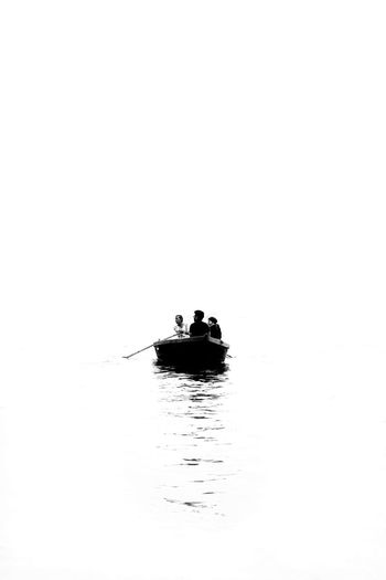 Silhouette man on boat in sea against sky