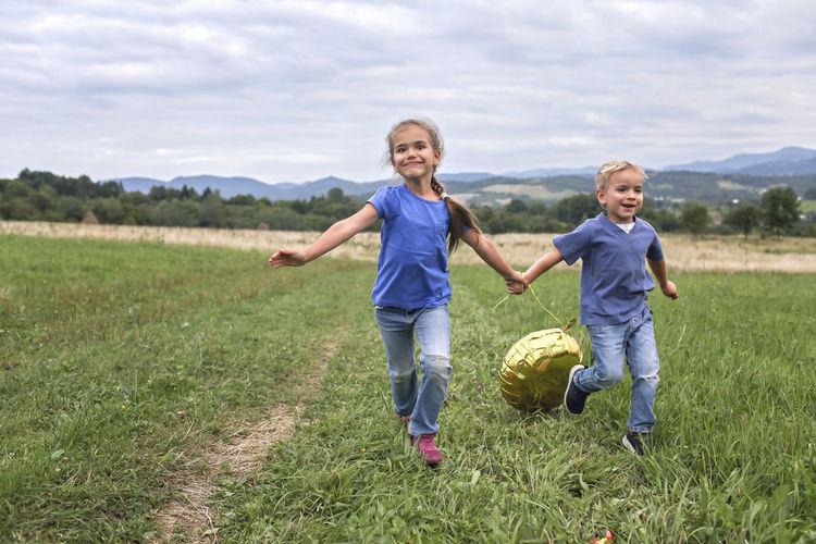 Full length of happy boy running on grass