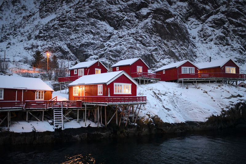 House by frozen lake by houses against snowcapped mountains during winter