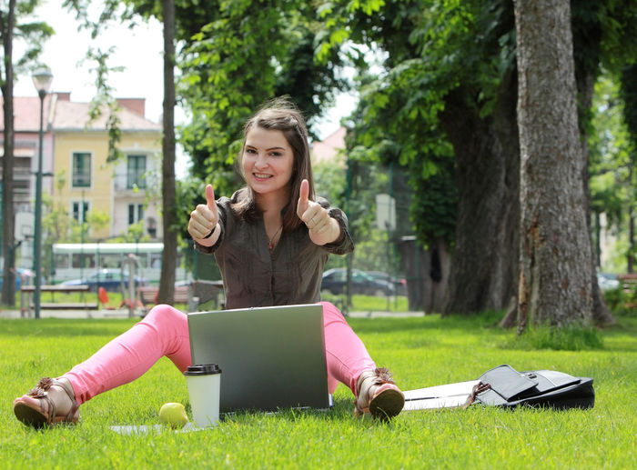 Happy young woman with a laptop in the grass in an urban park. Technology Grass Wireless Technology Communication Smiling Computer Front View One Person Laptop Using Laptop Happiness Emotion Outdoors Lifestyles Thumbs Up Success Successful Young Woman Woman Achievement Happiness Student Learning