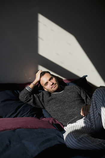 Young man lying on bed at home