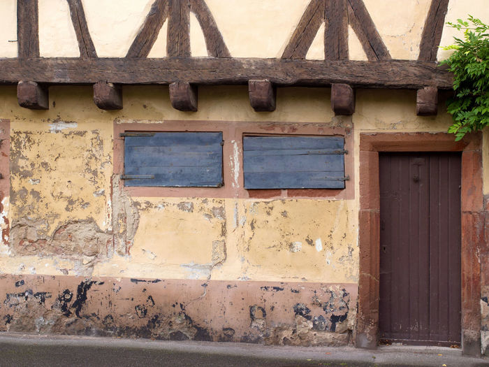 Old house facade in Wissembourg/France Alsace France Alsace-Lorraine Blind Blinds Brown Cities City Door Doors France House Facade House Facades House Wall Old Buildings Peeling Off Shutter Shutters Town Towns Travel Destinations Vosges Weathered Window Windows Wissembourg