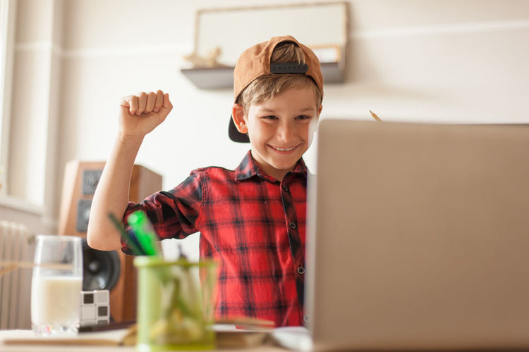 Cheerful boy celebrating his success while using computer in the living room.