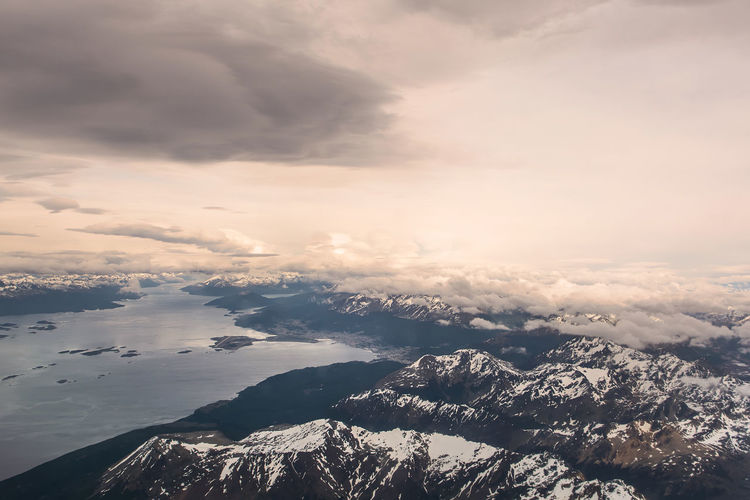 Aerial view of sea and mountains against dramatic sky