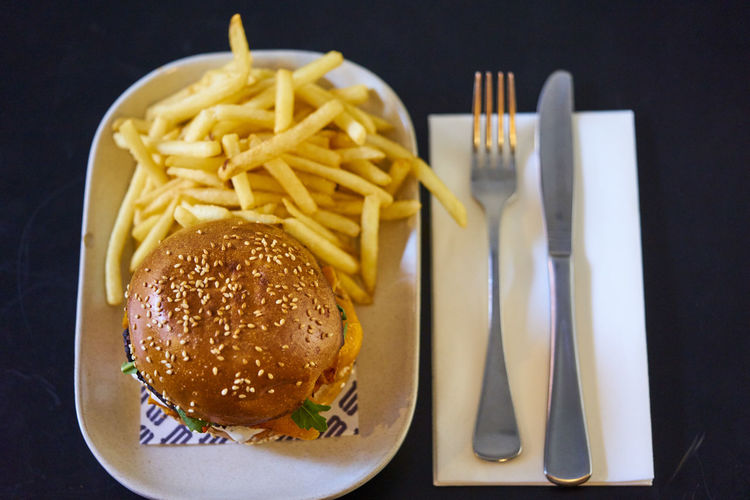Bread Bun Burger Close-up Eating Utensil Fast Food Fast Food French Fries Food Food And Drink Fork French Fries Freshness Fried Hamburger Indoors  No People Potato Prepared Potato Ready-to-eat Sandwich Snack Still Life Table Knife Take Out Food Unhealthy Eating