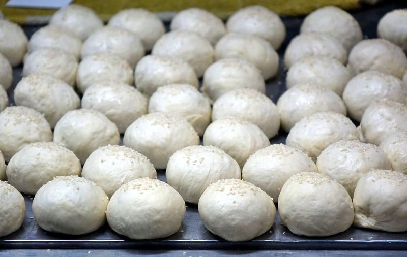 Fresh buns with sesame seeds are ready for baking Tray Asian Food Bakery Buns Chinese Dumpling Chinese Food Dough Dumpling  Food Freshness Large Group Of Objects Raw Food Sesame Seeds