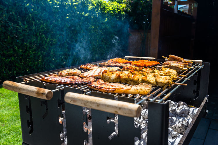 Different types of meat fried on the home grill, standing on a home garden on the paving stone.