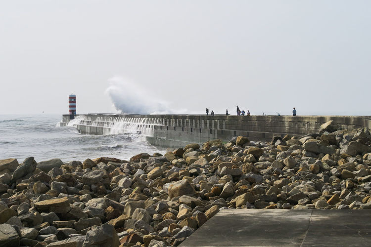 big waves of the atlantic ocean breaking over harbor wall in porto, portugal Light House Wall Harbor Atlantic Ocean Big Waves Stone Coastline Nature Water Water Spraying Sea RISK Danger Sky Building Exterior