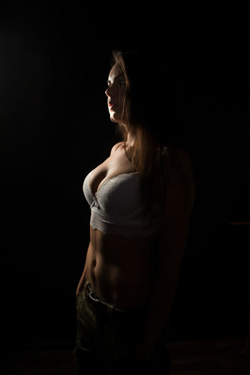 Young woman looking away against black background