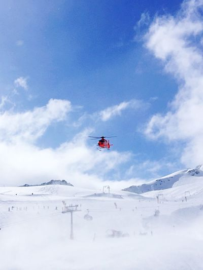 Low angle view of person paragliding on snowcapped mountain against sky