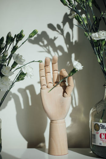 Close-up of hand holding flower vase on table