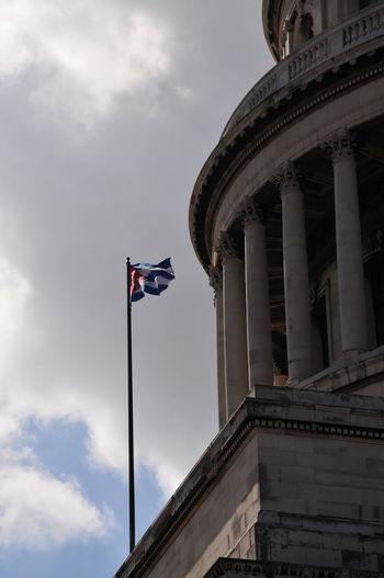 Low angle view of cuban flag by historic building against sky