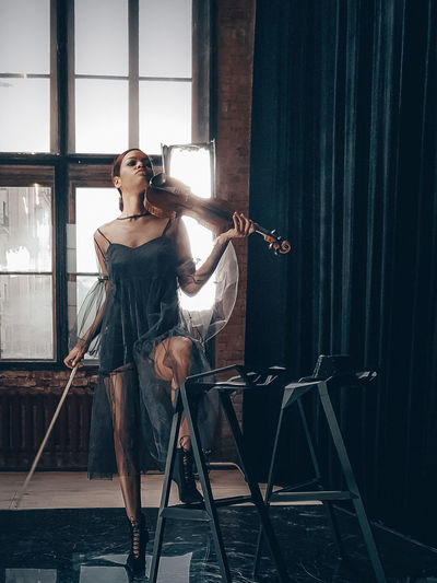 Woman with violin standing in home