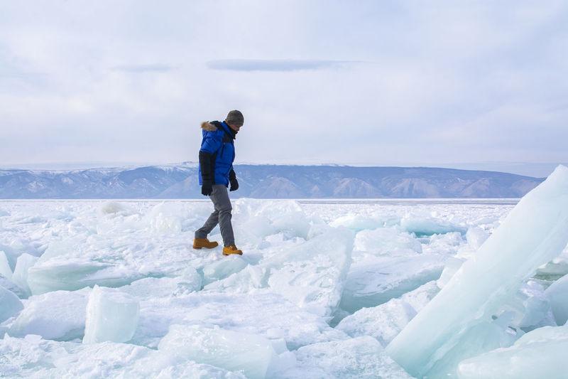 Full length of man walking on glacier on frozen lake against sky