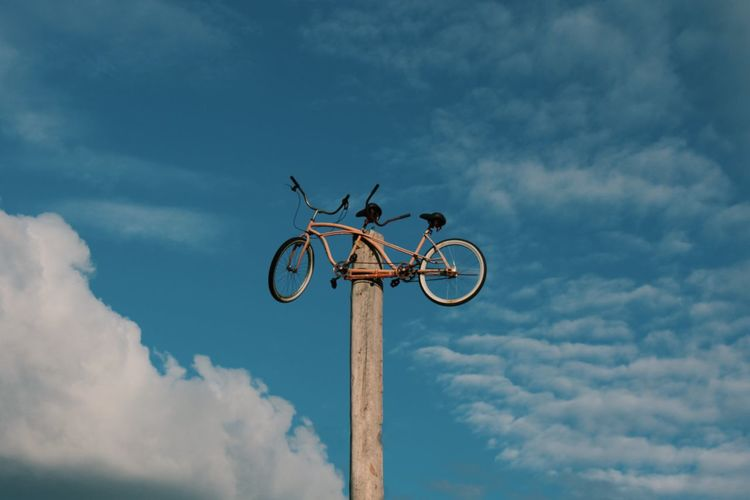 Low angle view of bicycle on pole against sky