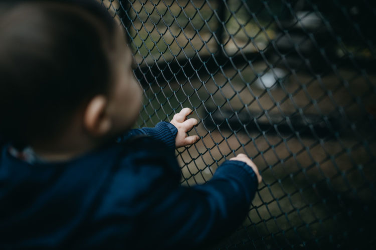 Rear view of boy looking through chainlink fence