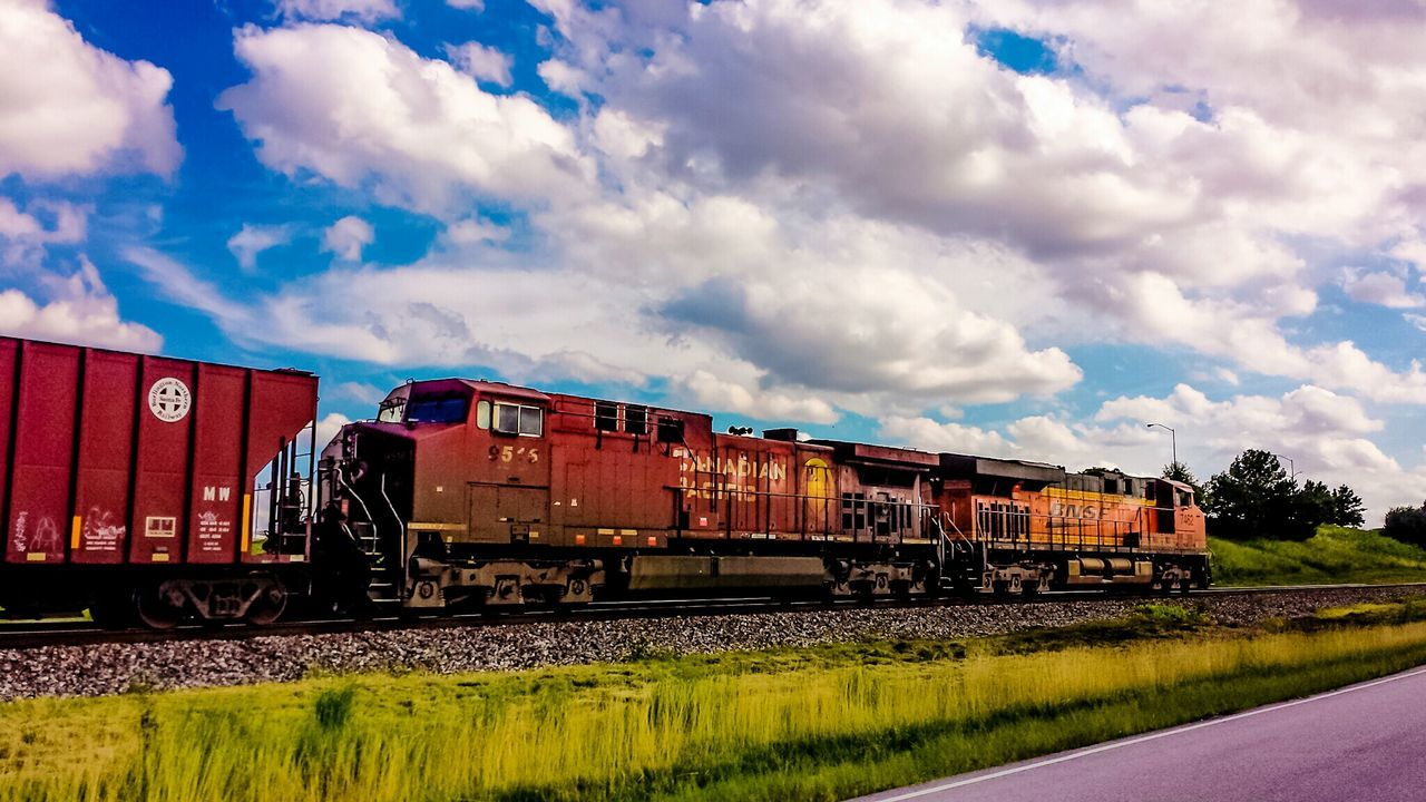 transportation, mode of transport, cloud - sky, sky, train - vehicle, freight transportation, day, rail transportation, outdoors, railroad track, red, no people, cargo container, grass, locomotive
