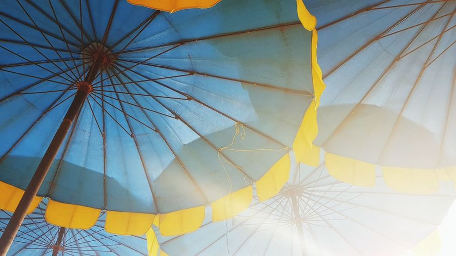 Low Angle View Of Parasols Against Sky During Sunny Day