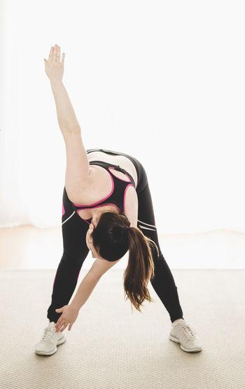 Full length of woman exercising against white background