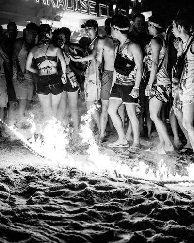 Line of Fire Group Of People Real People Large Group Of People Illuminated Fire Rope Flames Flames & Fire Beach Party Party - Social Event Shorts Black And White Headband Japanese  Smoke Glowing Looking Back Danger LINE Bags Leisure Activity Night Crowd