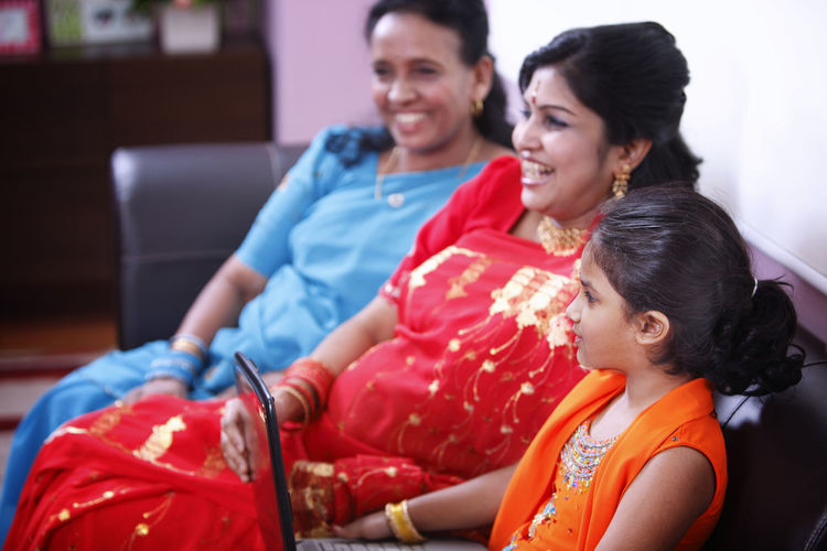 mother teaching daughter using computer At Home Happiness In A Row Indian Ethnicity Mother & Daughter Red Sitting Traditional Clothing Bonding Colorful Communication Computer Connection Granddaughter Grandmother Laptop Sari Smiling Sofa Technology This Is Family Three People Togetherness Using Laptop Wireless Technology