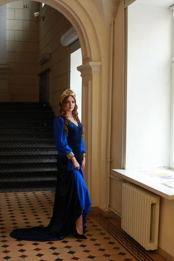 Full Length Portrait Of Teenage Girl Wearing Royal Blue Dress Standing At Palace
