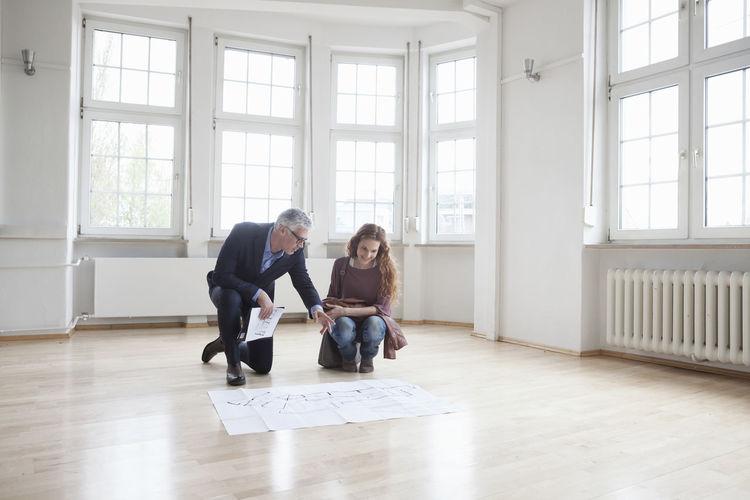 Full length of friends standing on hardwood floor at home