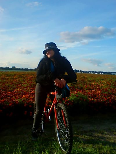 Woman with bicycle on flower field against sky
