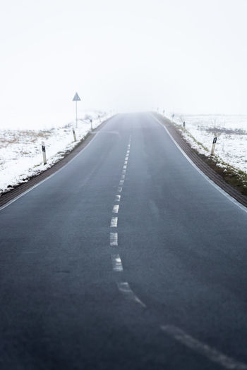 Surface level of road against clear sky during winter