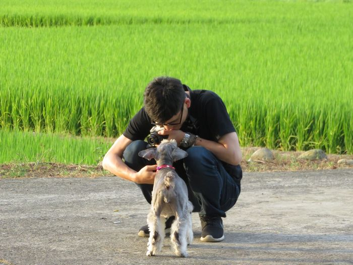 Young Man Looking At Dog While Crouching On Road Against Plants