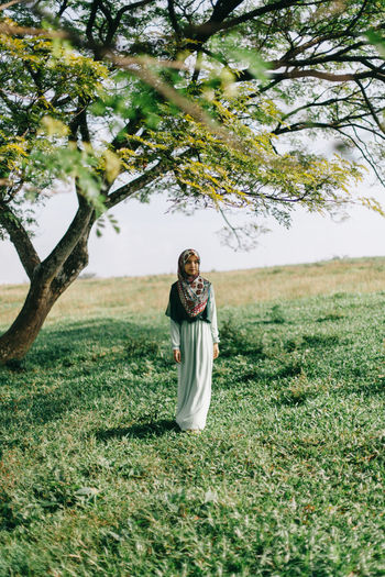 Young woman standing on field against trees