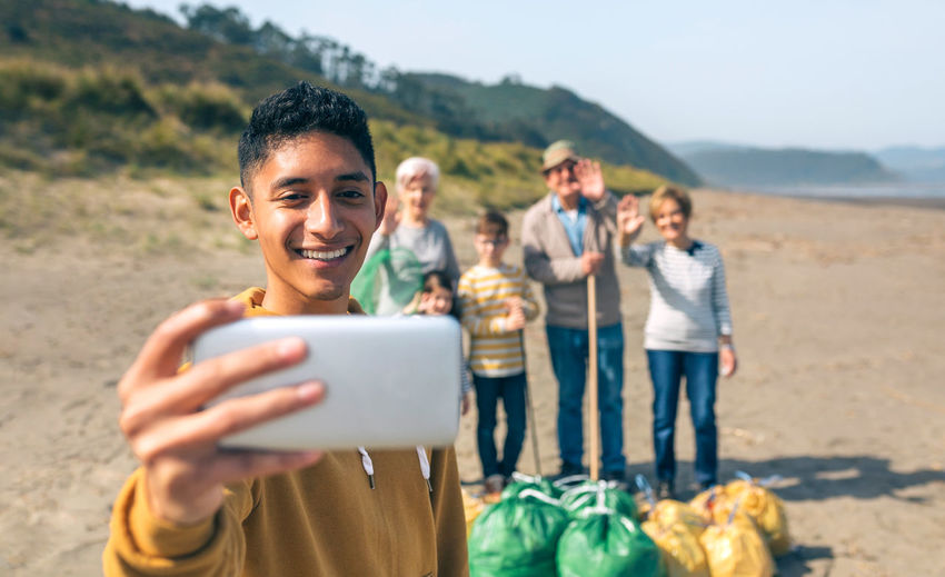 Smiling young man photographing with family while cleaning beach
