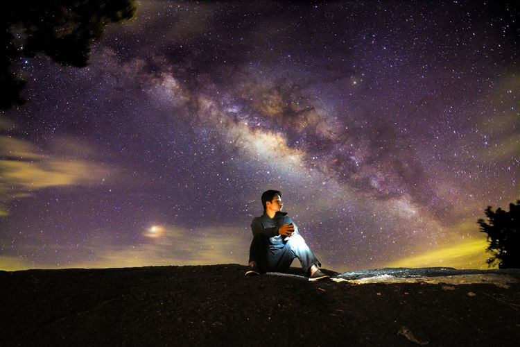 Full length of man sitting against sky at night