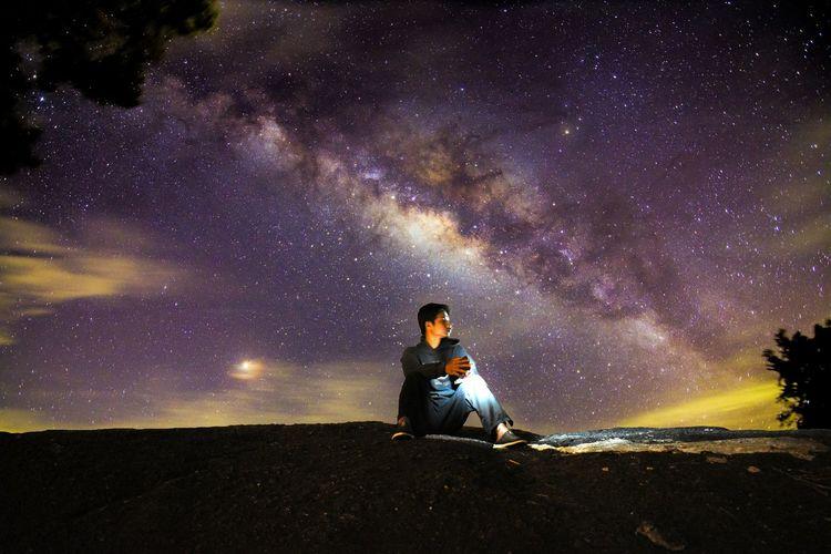 Full Length Of Man Sitting Against Sky At Night