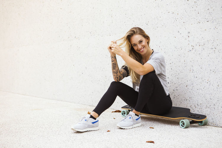 Full Length Portrait Of Smiling Young Woman Sitting On Skateboard Against Wall