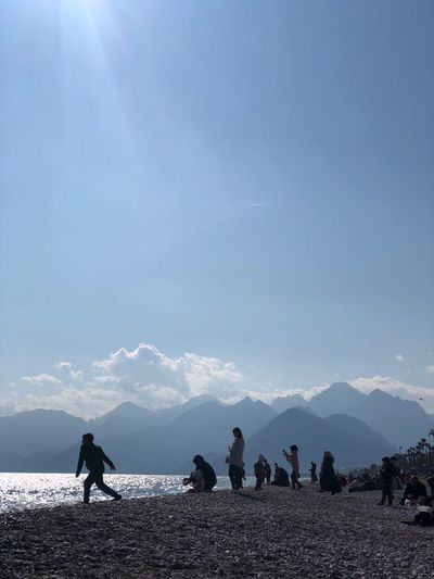 People enjoying at beach against sky