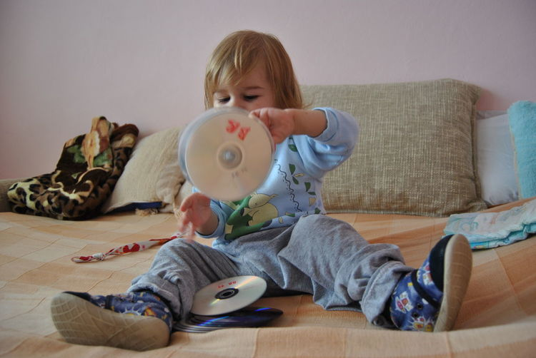 Cute boy playing with compact discs on bed at home