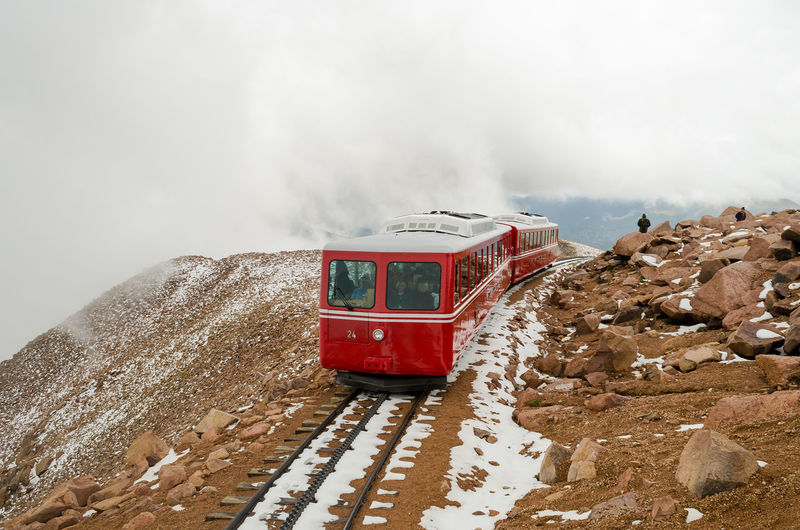 Cloud - Sky Cold Temperature Day Mountain Mountain Train Nature Non-urban Scene Pikes Peak Summit Red Riverbank Rock - Object Scenics Season  Sky Snow Tourism Tranquil Scene Tranquility Transportation Travel Vacations Vibrant Color Water Winter