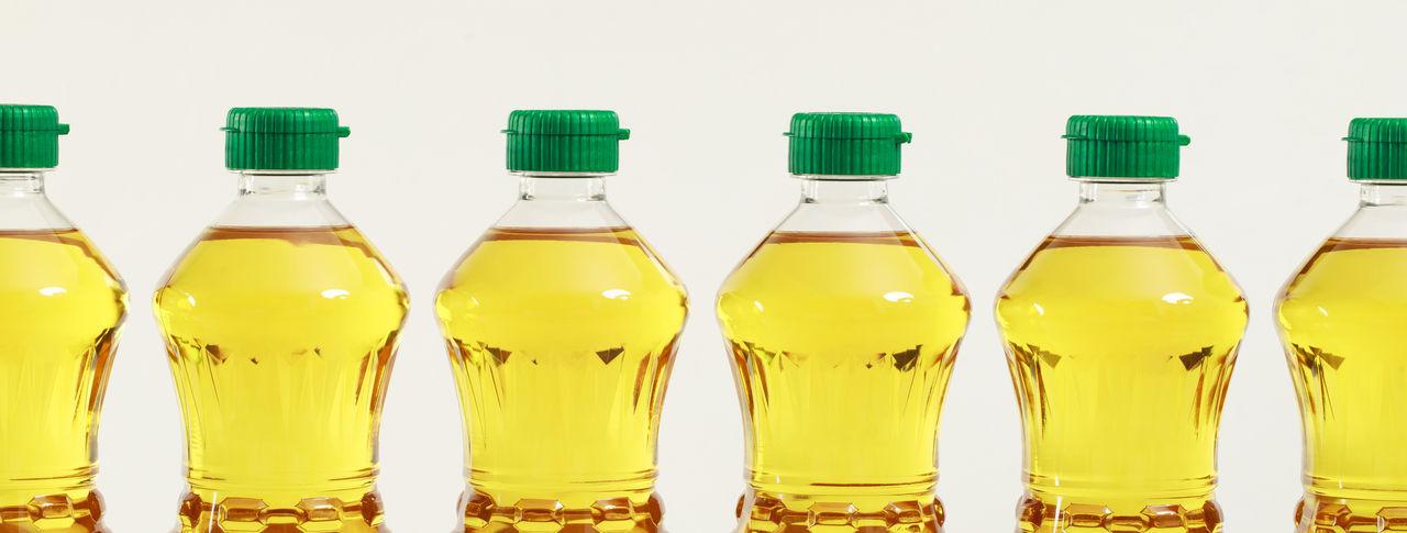Panoramic shot of glass bottles against white background