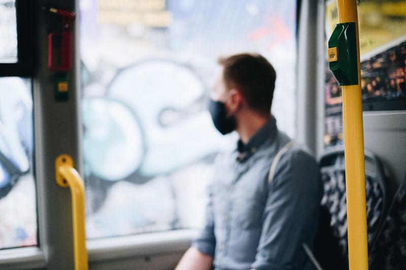 Defocused image of man wearing mask looking away while sitting in bus
