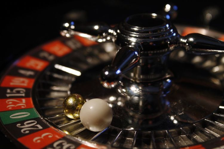 Close-up of roulette wheel with balls at casino