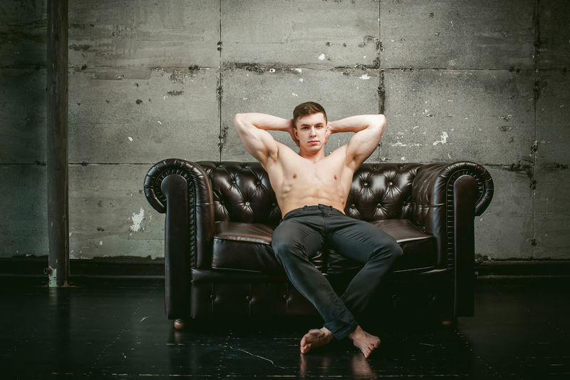 Portrait Of Shirtless Muscular Man Sitting On Armchair Against Wall