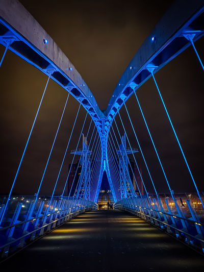 Illuminated bridge against blue sky at night