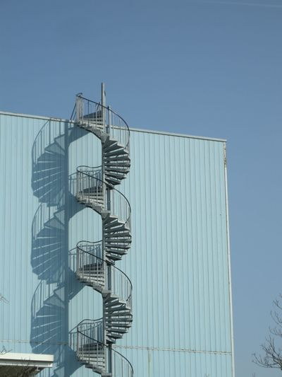 Low angle view of metallic spiral staircase by wall against clear sky