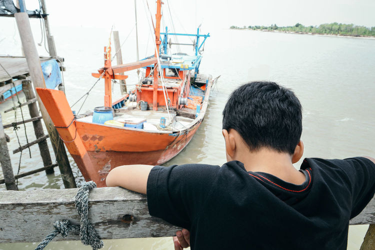 High angle view of boy against moored boat on sea