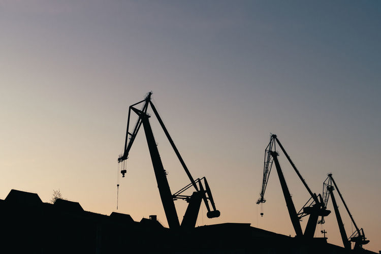 Low angle view of silhouette cranes against clear sky at sunset