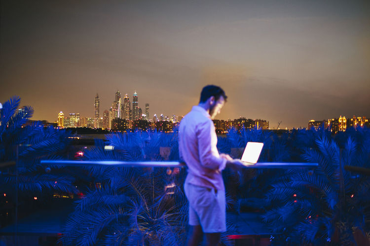 Full length of man standing by illuminated buildings against sky at night
