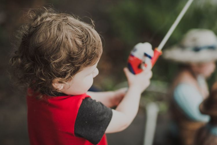 Close-up of boy holding fishing rod while standing outdoors